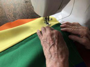 Elena cosiendo una bandera LGBTI