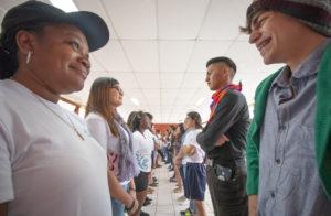 Dos hileras de jóvenes, entre ambos grupos se ven a los ojos. En primer plano dos jóvenes, un chico y una chica se ven y sonríen.